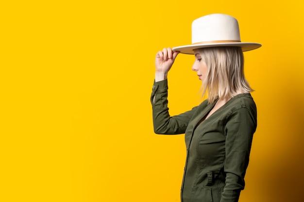노란 벽에 모자와 녹색 셔츠에 금발 여자