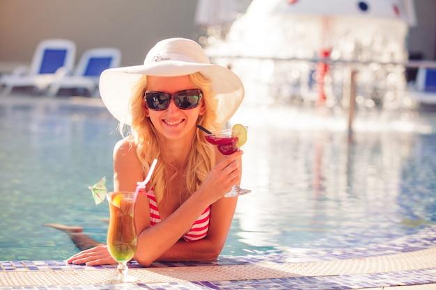 Блондинка в шляпе у бассейна