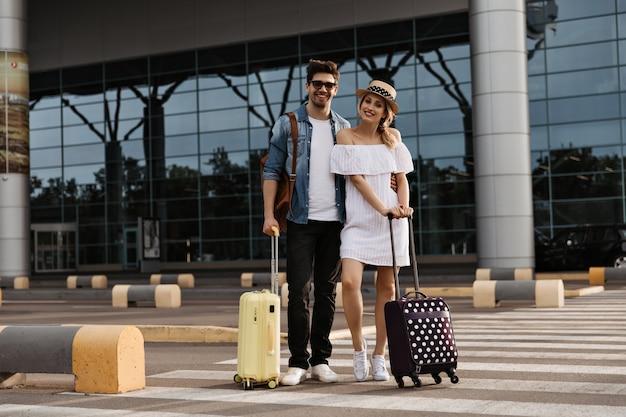 Блондинка в шляпе, белом платье и брюнетка в джинсовой куртке, солнцезащитных очках улыбается и позирует с чемоданами возле аэропорта