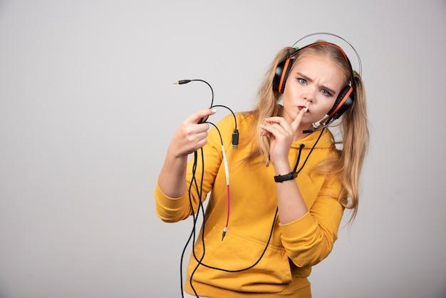 コードを保持しているヘッドフォンで金髪の女性。