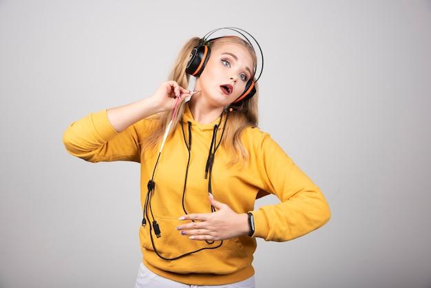 彼女の胃を保持しているヘッドフォンで金髪の女性。