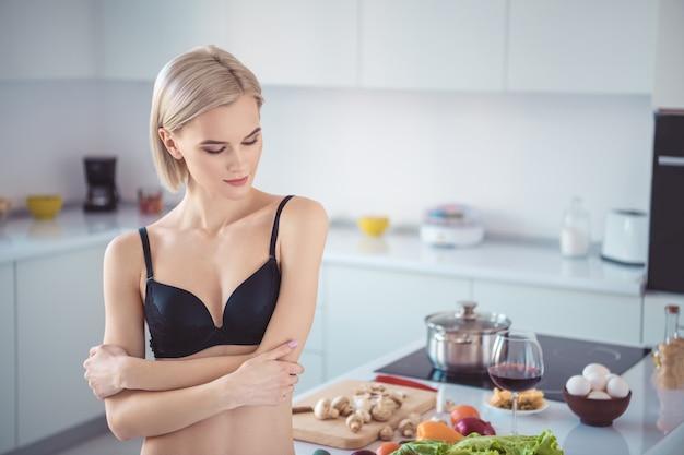 キッチンでポーズをとる彼女のランジェリーのブロンドの女性