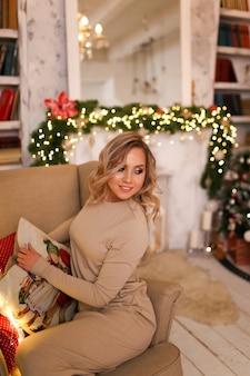 笑顔と肘掛け椅子に座っている暖炉と木のそばで楽しんでいるホームドレスのブロンドの女性