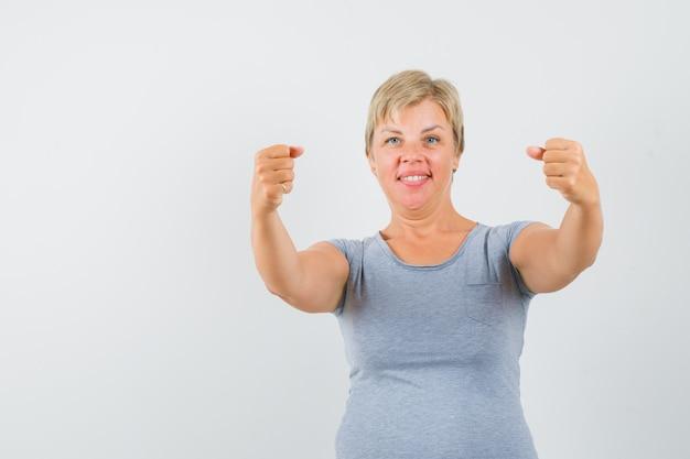 Блондинка в голубой футболке сжимает кулаки и выглядит счастливой, вид спереди.