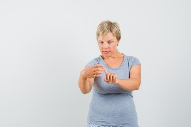 水色のtシャツを着た金髪の女性が、電話で何かをズームするのが好きで、焦点を合わせて正面から見ています。