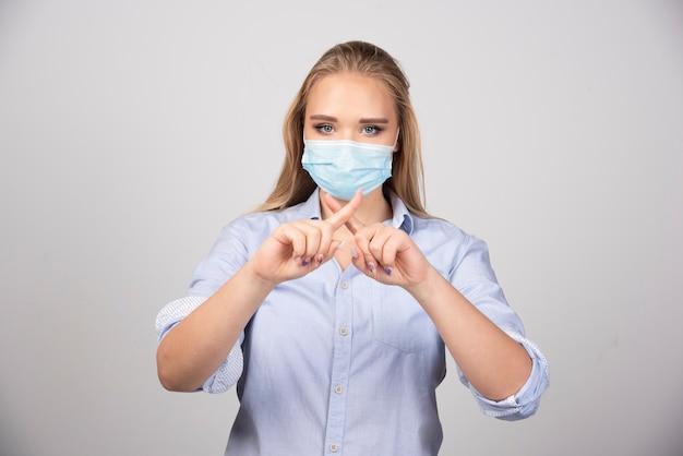 교차 손가락을 보여주는 의료 마스크에 아름 다운 금발 여자입니다.