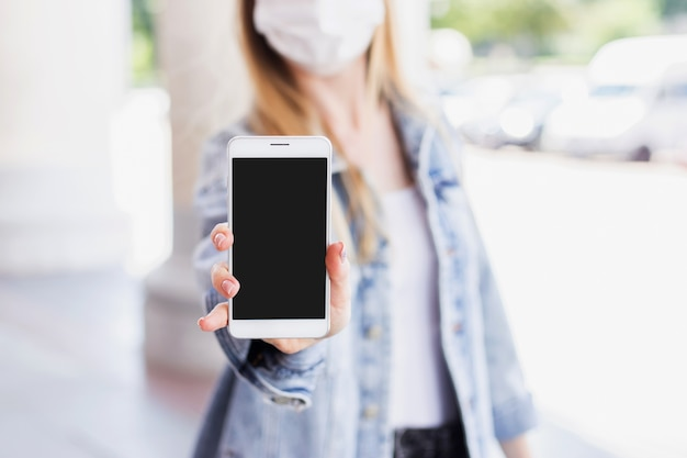 医療マスクのブロンドの女性は空白のスマートフォンの画面を示しています