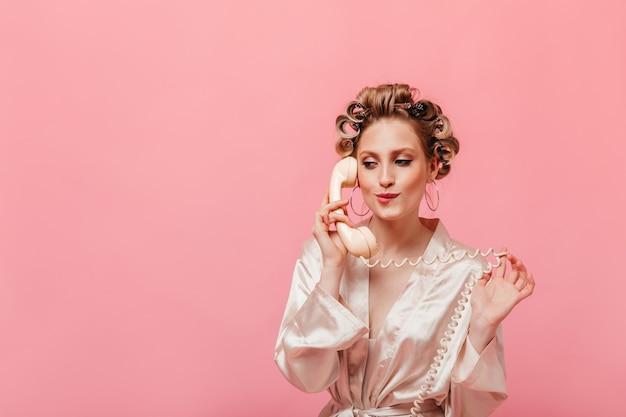 분홍색 가운에 금발의 여자가 그녀의 입술을 물고 들떠 전화로 이야기