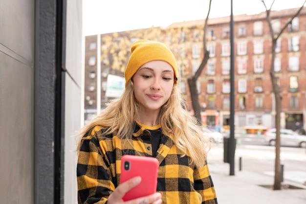 格子縞のシャツと路上で携帯電話のブロンドの女性幸せな笑顔