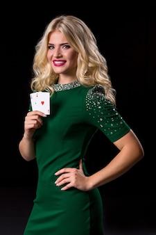 도박을 위해 카드를 들고 포즈를 취하는 금발의 여자