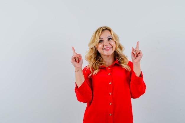 人差し指で上向きと幸せそうに見える赤いブラウスのブロンドの女性
