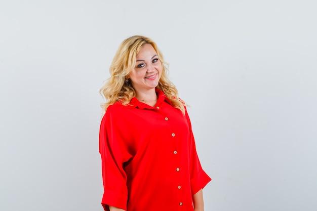 赤いブラウスを着た金髪の女性がまっすぐ立ってカメラに向かってポーズをとって、きれいに見える、正面図。