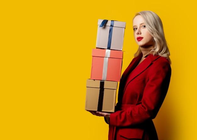 黄色の壁にギフトボックスと赤いコートを着た金髪の女性