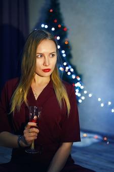 家で白ワインまたはシャンパンのガラスと赤いドレスを着た金髪の女性。クリスマスツリー。新年の飾り