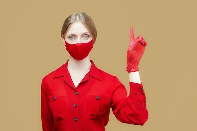 赤い手袋とマスクをした金髪の女性が人差し指で方向を指しています。 covid19コロナウイルスの予防の概念。
