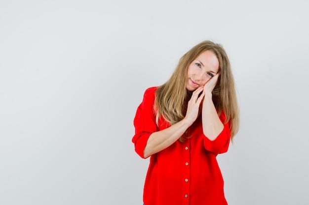 枕のように手のひらに寄りかかってエレガントに見える赤いシャツのブロンドの女性、