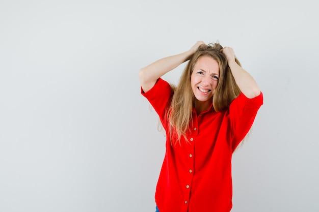 Блондинка в красной рубашке рвет волосы и задумчиво смотрит,