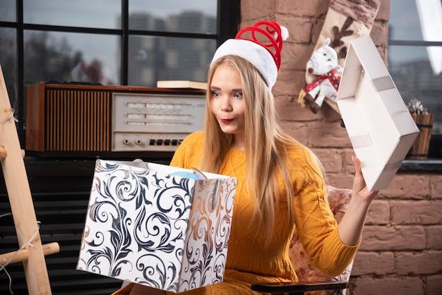 Белокурая женщина в шляпе санты смотря подарочную коробку.