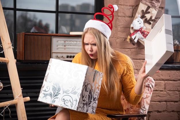Блондинка женщина в шляпе санты, глядя внутрь подарочной коробки.
