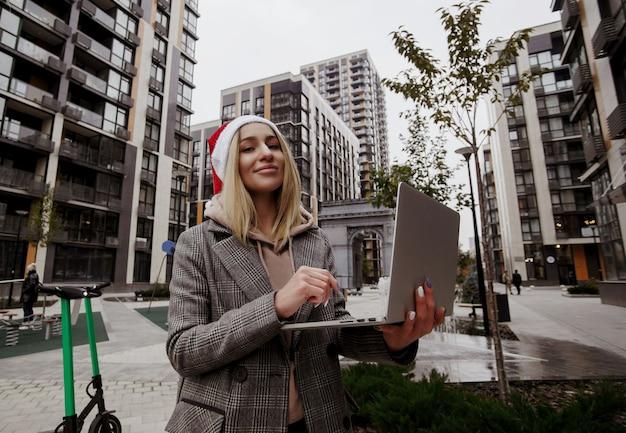 外に座ってラップトップで作業しているカジュアルな服を着てサンタの帽子をかぶった金髪の女性。メリークリスマス、そしてハッピーニューイヤー!新鮮な空気で彼女の仕事をしている若いフリーランサーの女性。