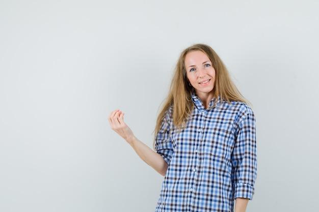 Блондинка в рубашке делает итальянский жест и выглядит веселой