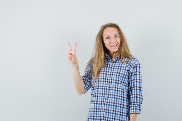勝利のサインを示し、陽気な探しているシャツのブロンドの女性、