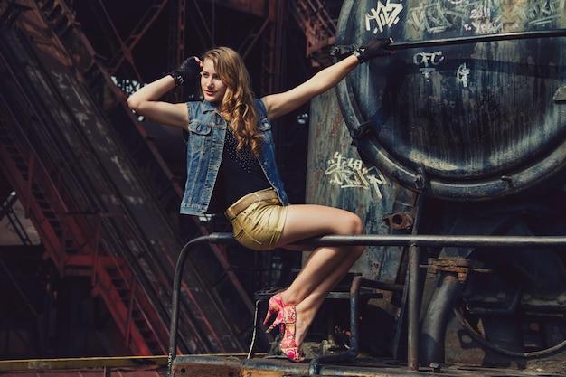 古い廃工場でショートパンツとハイヒールで金髪の女性。