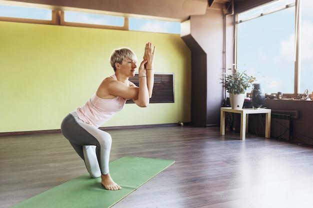 スポーツウェアのブロンドの女性、ヨガの練習、スタジオのマットの上に立って、ガルダサナ運動、ワシのポーズを実行します