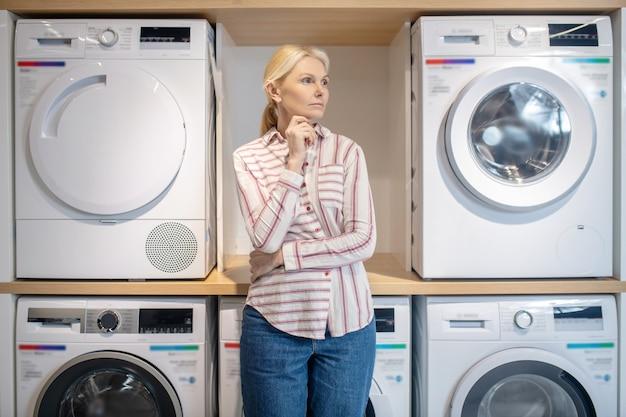 洗濯機の近くに立っている縞模様のシャツのブロンドの女性