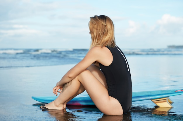Блондинка в купальнике с доской для серфинга на пляже