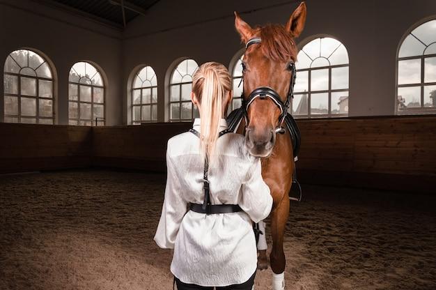 Блондинка в виде всадника со спины. скачки и концепция конного спорта.