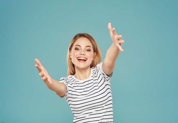Блондинка в футболке, жестикулируя руками на синем фоне, обрезанный вид копией пространства