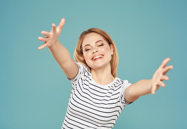 青い背景のトリミングされたビューコピースペースに彼女の手で身振りで示すtシャツのブロンドの女性。