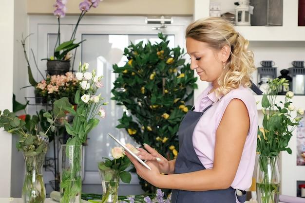 Блондинка в униформе принимает онлайн-заказ букетов цветов от покупателей. продавец флориста женщина работает на планшете в цветочном магазине, вид сбоку. она стоит возле цветов в вазах. цветочная бизнес-концепция.