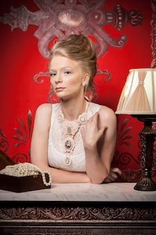 빅토리아 드레스와 인테리어에 금발 여자입니다. 풍부한 라이프 스타일. 빈티지와 역사