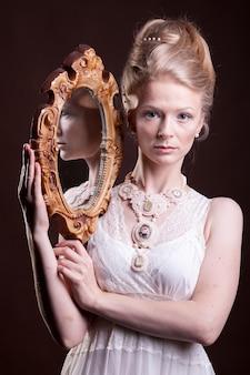 Mirrod를 손에 들고 빅토리아 드레스에 금발 여자. 풍부하고 빈티지합니다. 럭셔리와 우아함. 스튜디오 사진