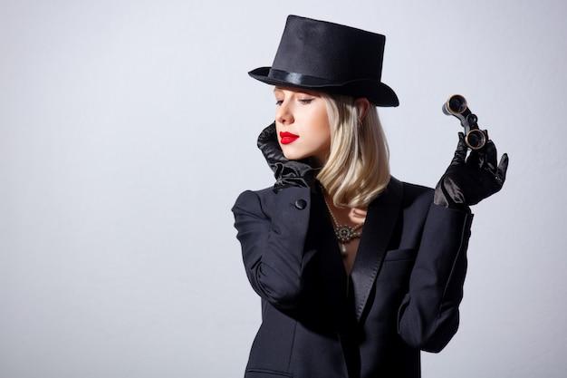 Блондинка в винтажном черном пиджаке и цилиндре с оперными очками