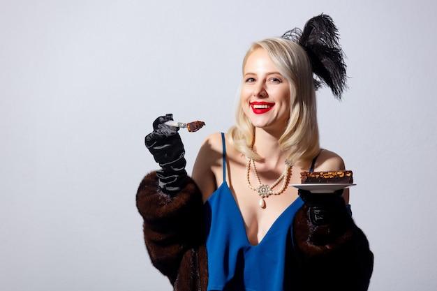 ヴィンテージの青いドレスと毛皮のコートのケーキで金髪の女性