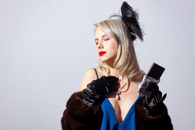 ヴィンテージの青いドレスとダークチョコレートバーの毛皮のコートで金髪の女性