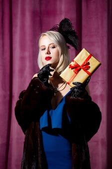 ヴィンテージの青いドレスと毛皮のコートのギフトボックスで金髪の女性