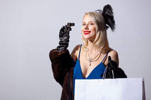 Блондинка в винтажном синем платье и шубе с оперными очками и хозяйственной сумкой