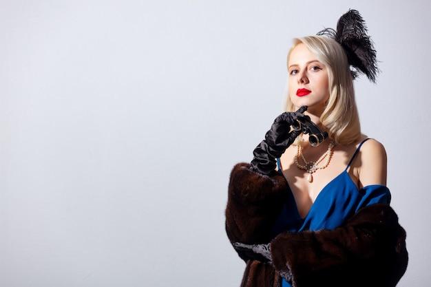 Блондинка в винтажном синем платье и шубе с оперными очками