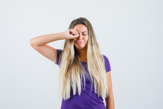 Блондинка в фиолетовой футболке трет глаза, плача и обижаясь, вид спереди.
