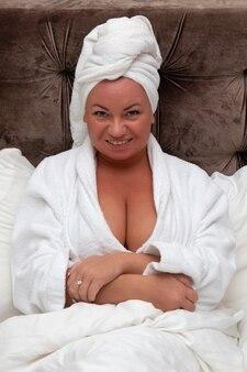 침대에 흰 가운에 금발 여자