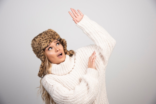 어딘가에 찾고 겨울 모자에 금발 여자입니다.