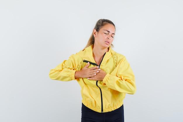 노란색 폭격기 재킷과 검은 색 바지에 금발의 여자가 심장 통증이 있고 지쳐 보입니다.