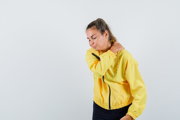 黄色のボンバージャケットと黒のズボンのブロンドの女性は、肩の痛みがあり、疲れ果てているように見えます