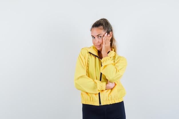 Блондинка в желтом бомбере и черных штанах, опираясь щекой на ладонь, думает о чем-то и выглядит задумчиво