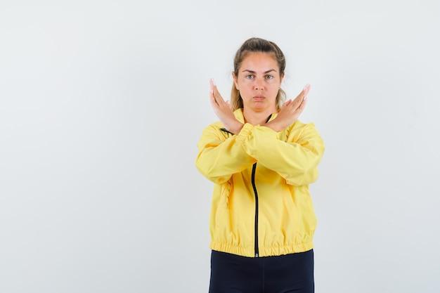 노란색 폭격기 재킷과 제한 제스처를 보여주는 검은 바지에 금발의 여자와 심각한 찾고