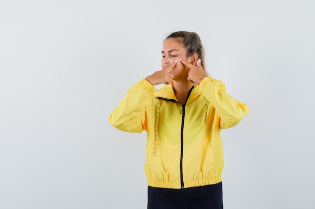 黄色のボンバージャケットと黒のズボンでにきびを絞って集中して見える金髪の女性